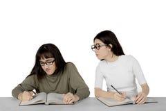 Studente asiatico che sbircia al suo compagno di classe Fotografia Stock