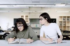 Studente asiatico che sbircia il suo compagno di classe nell'aula Fotografie Stock