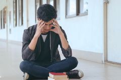 Studente asiatico che si siede sulla stanza anteriore, frustrata sul suo lavoro e immagini stock