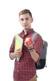 Studente asiatico che sta sul bianco con i libri e la mela Di nuovo a Sc Immagini Stock