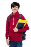 Studente asiatico con lo zaino ed il manuale Fotografia Stock