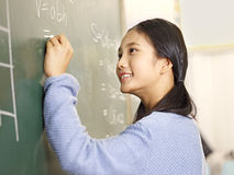 Studente asiatico della scuola elementare che risolve un problema per la matematica Immagine Stock