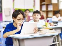 Studente asiatico della scuola primaria che utilizza compressa nell'aula immagini stock libere da diritti
