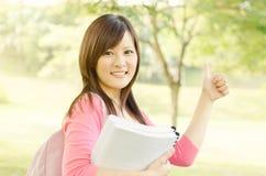 Studente asiatico della studentessa di college che mostra pollice su Fotografia Stock Libera da Diritti