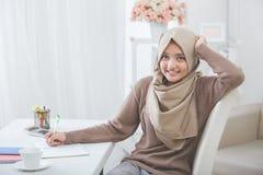 Studente asiatico femminile bello con hijab che fa compito Immagini Stock