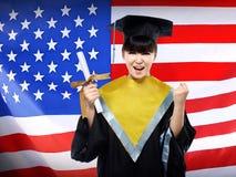 Studente asiatico femminile felice con il fondo della bandiera di U.S.A. Fotografia Stock