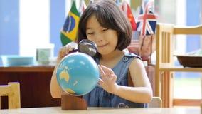 Studente asiatico piccolo che esamina globo archivi video