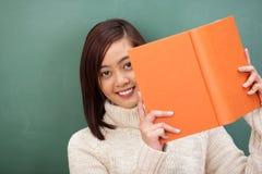 Studente asiatico sorridente che scruta intorno al suo manuale Fotografia Stock