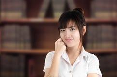 Studente asiatico in uniforme con il fondo confuso delle biblioteche Fotografia Stock Libera da Diritti