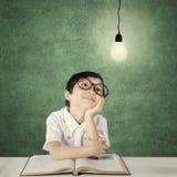 Studente astuto della scuola primaria che esamina lampadina Fotografia Stock Libera da Diritti
