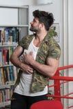 Studente atletico Reading di forma fisica dal libro in biblioteca Fotografie Stock