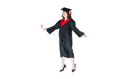 Studente attraente in cappuccio di graduazione con il salto del diploma isolato Fotografia Stock Libera da Diritti