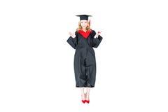 Studente attraente in cappuccio di graduazione con il salto del diploma isolato Fotografia Stock