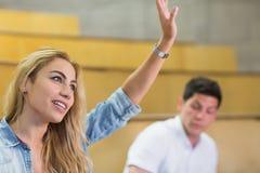 Studente attraente che solleva mano durante la classe Immagine Stock Libera da Diritti