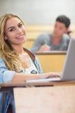 Studente attraente sorridente che per mezzo del computer portatile Fotografia Stock Libera da Diritti