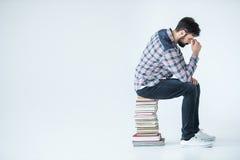 Studente barbuto che si siede sul mucchio dei libri su bianco con lo spazio della copia Fotografie Stock