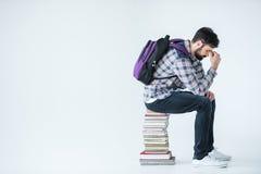 Studente barbuto che si siede sul mucchio dei libri su bianco con lo spazio della copia Immagini Stock