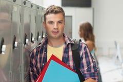 Studente bello allegro che sta accanto all'armadio Fotografia Stock Libera da Diritti