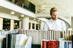 Studente bello che cerca un libro in una biblioteca Immagini Stock Libere da Diritti