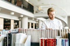 Studente bello che cerca un libro in una biblioteca Fotografia Stock Libera da Diritti