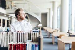 Studente bello che cerca un libro in una biblioteca Immagini Stock