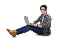 Studente bello che per mezzo del computer portatile Fotografie Stock