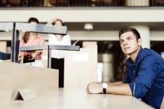 Studente bello che si siede ad uno scrittorio e ad uno studio Immagini Stock