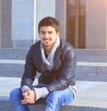 Studente bello del giovane che si siede sui punti dell'istituto universitario Fotografia Stock