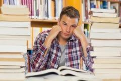 Studente bello irritato che studia fra i mucchi dei libri Fotografie Stock