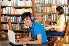 Studente in biblioteca con il computer portatile Immagini Stock Libere da Diritti