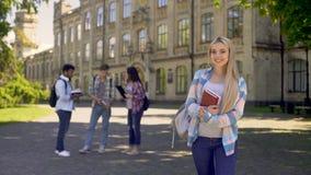 Studente biondo allegro allegro che sorride esaminando macchina fotografica, istruzione di qualità archivi video