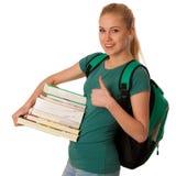 Studente biondo con la pila di libri e di zaino, felice di ottenere kn Immagini Stock