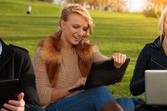 Studente biondo con la risata del computer portatile Fotografia Stock