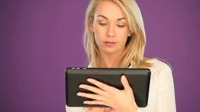 Studente biondo felice che lavora ad una compressa archivi video