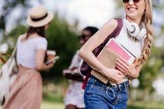 Studente biondo sorridente con le cuffie che tengono i libri mentre amici che parlano dietro nel parco Immagine Stock
