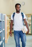 Studente With Books Looking via in biblioteca Immagini Stock Libere da Diritti