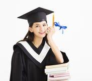 Studente in cappuccio di graduazione con la pila di libri Fotografia Stock Libera da Diritti