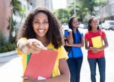 Studente caraibico che indica alla macchina fotografica nella città con gli amici Fotografia Stock
