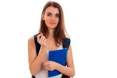 Studente castana abbastanza giovane con lo zaino ed i libri in sue mani che posano sulla macchina fotografica isolata su fondo bi Fotografia Stock
