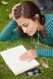 Studente casuale calmo che si trova sull'erba che legge un libro Immagine Stock Libera da Diritti
