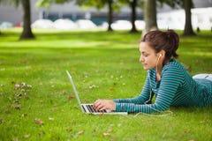 Studente casuale calmo che si trova sull'erba facendo uso del computer portatile Immagine Stock Libera da Diritti