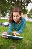 Studente casuale calmo che si trova sull'erba facendo uso della compressa Immagine Stock
