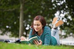 Studente casuale calmo che si trova sulla lettura dell'erba Fotografia Stock Libera da Diritti