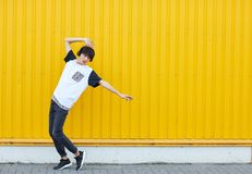Studente casuale che balla alla musica su un fondo giallo della parete Concetto attivo di stile di vita Copi lo spazio fotografia stock libera da diritti