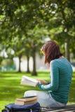 Studente casuale che si siede sulla lettura del banco Fotografie Stock Libere da Diritti