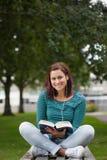 Studente casuale sorridente che si siede sulla lettura del banco Fotografie Stock