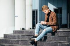 Studente caucasico che si siede sui punti e che per mezzo dello smartphone Immagini Stock Libere da Diritti