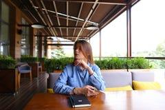 Studente caucasico femminile che si siede al caffè con il taccuino sulla tavola e che per mezzo dello smartphone Fotografia Stock