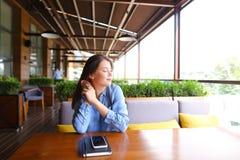 Studente caucasico femminile che si siede al caffè con lo smartphone ed il taccuino sulla tavola Fotografia Stock Libera da Diritti