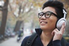 Studente che ascolta la musica sulla città universitaria dell'istituto universitario Immagine Stock